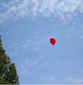 RED HELIM BALLOON RISING IN THE AIR