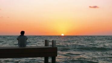 MAN SITTING ON PIER AT SUNSET