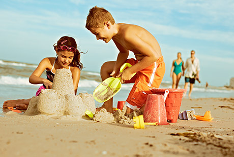TWO KIDS BUILDING SANDCASTLE