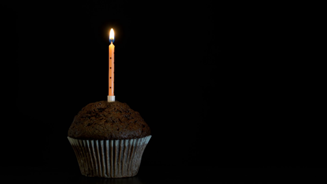 footage-muffin-with-a-candle-close-up-on-black-background-4k-video_hfs9xembl_thumbnail-full01