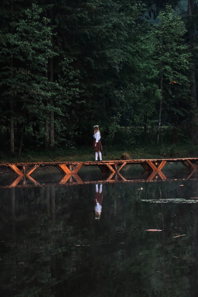 three line tales, week 257: a woman walking over a narrow bridge over a body of water